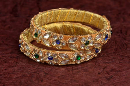 Indian golden Bangles. Bracelet with diamonds and stones on a textured background, Indian Traditional Jewellery,Style, fashion and design of jewelry