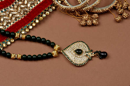 Antique jewellery on a brown background, Golden scarf, Gold bracelet,jewelry background, Gold necklace, Gold earrings, finger ring.Style, fashion and design of jewelry. indian traditional jewellery
