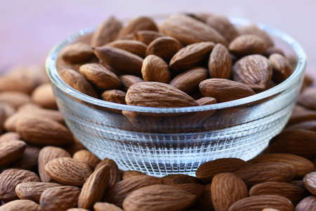 Almonds in bowl, Group of almond nuts isolated on white background. Depth of field