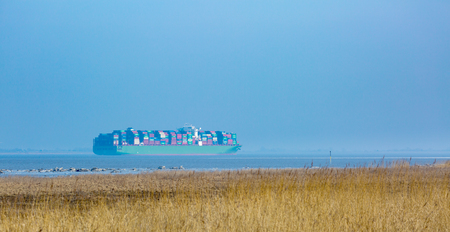 A fully loaded container ship sails on the Elbe river estuary to the port of Hamburg - nature reserve near Freiburg (Elbe), Germany Stock Photo