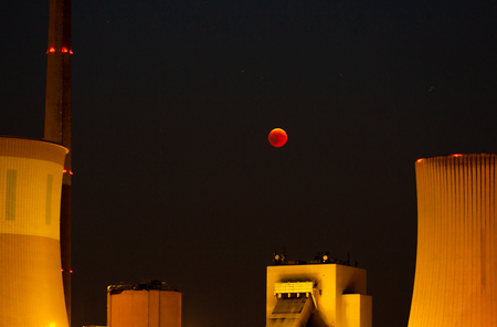 Lunar eclipse - it seems as if the red moon is directly above the power plant - Großkrotzenburg, Germany