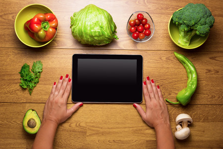 brocoli: Top view of fresh vegetables on rustic wood table and tablet  used by a woman