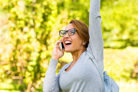 mooie vrouw vieren succes nieuws met armen omhoog in een park Stockfoto