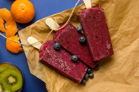 Homemade popsicles style vintage fruits, blueberry, kiwi and mandarin flavor, top view Stock Photo