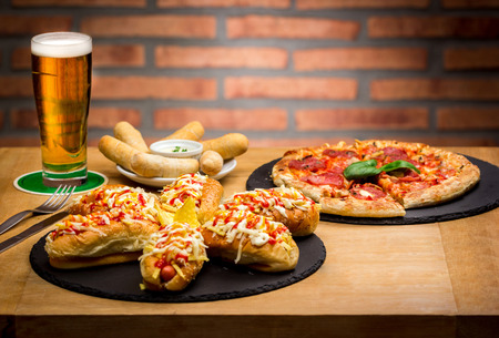 fast food and unhealthy eating concept. pizza, hot two tequeà± os