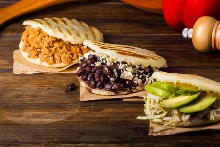 Arepas、木製のテーブルの上のラテン アメリカ料理の 3 つのタイプ