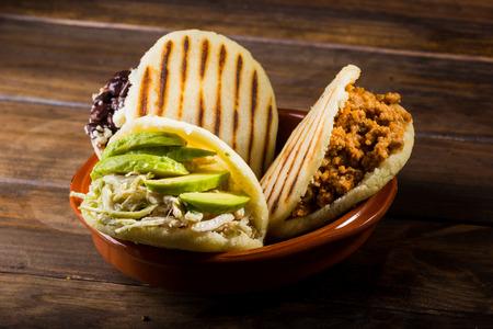 Three types of arepas, Latin American food on wood table