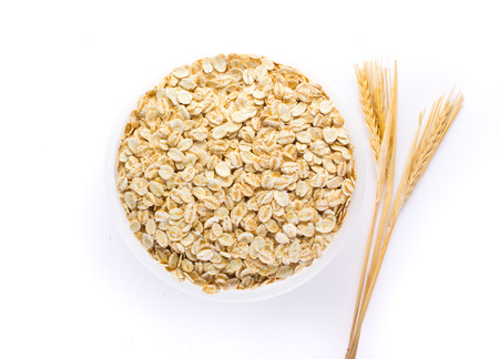 Oat flakes, uncooked oats in bowl on white background , Concept of healthy eating, vegan food, healthy food, breakfast. Stock Photo
