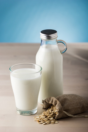 Glass of milk and sack of oats on a wooden table and blue background. daily food Stock Photo