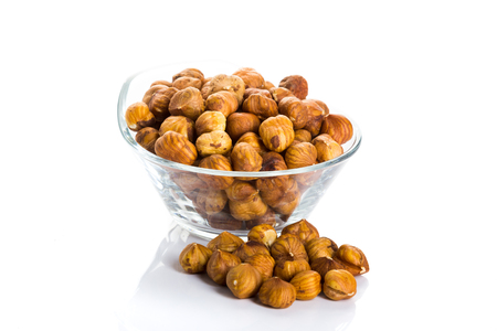 Group of peeled hazelnuts in a bowl on a white background Stock Photo