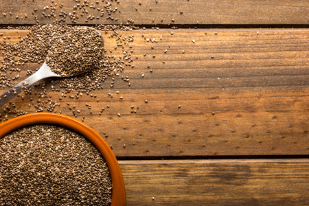 Group of chia seeds in a bowl on a wooden table.