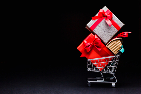 shopping cart with gifts on a black background Stock Photo