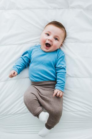 portrait d & # 39 ; un bébé âgé adorable bébé couché couché dans un lit de feuilles blanches Banque d'images