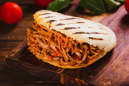 Freshly cooked Arepa with roasted meat on wood table Stock Photo