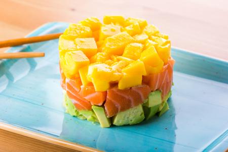 サーモンタルタル、アボカド、マンゴー、ラテン料理と日本食のミックス 写真素材