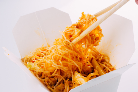 Noodles with chicken and vegetables in take-out box on white background