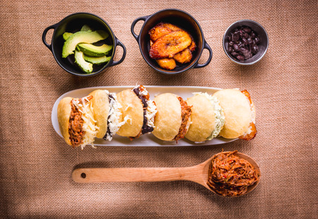 Different types of arepas, meat, black beans, cheese, fried plantain, typical South American food