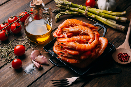 Rustic wooden table wiht prawns and some ingredients for seasoning and vegetables to mix them Stockfoto
