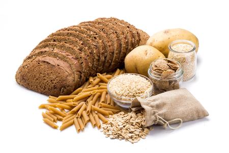 Grupo de alimentos integrales, carbohidratos complejos aislado sobre un fondo blanco. Foto de archivo