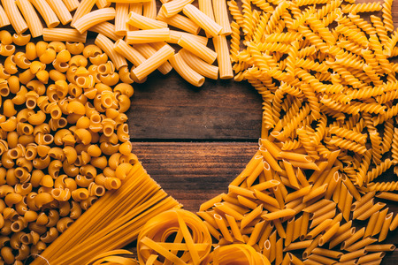 Table full of different types of pasta with a heart shape in the middle, pasta lovers Stock Photo