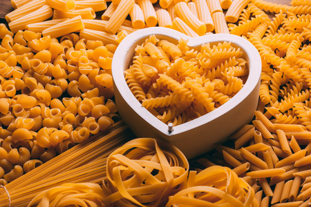 Table full of different types of pasta with a heart shape in the middle, pasta lovers 免版税图像