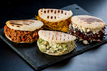 Venezuelan Latin American food, 4 arepas of different stuffing on a black table. Arepa with mechada meat, queen pepeada, black beans with white cheese and chicken Banco de Imagens