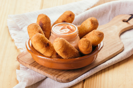 Latin-American appetizers called Tequeños made of fried corn filled with cheese with a pink sauce
