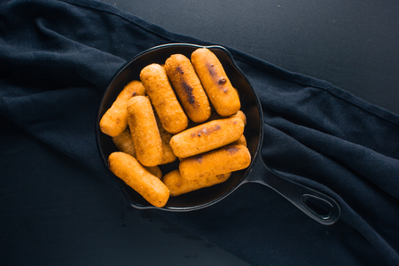 Top view of Cheese fingers inside a black pan ready to eat
