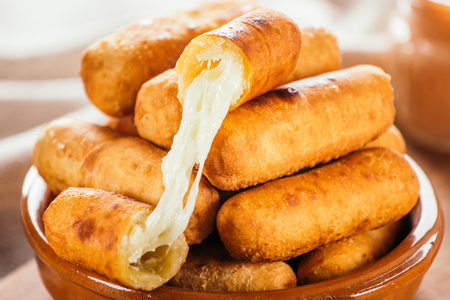 Cheese fingers, typical Venezuelan appetizer called Teque?os accompanied with a pink sauce on a wooden board