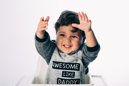 Little boy sitting with a winner expression on his face, on a white background