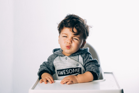 Little crying child sitting on his chair eating on a white background