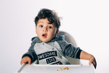 little 1 year old boy sitting with a very funny expression on his face, on a white background 版權商用圖片