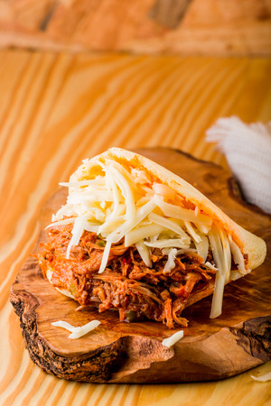 Roasted beef arepa on a wooden table