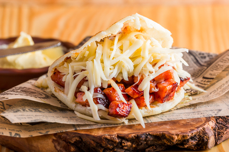 Arepa with fried pork and cheddar cheese ready to eat served on the table