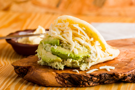 Typical Latin American food, arepa for breakfast with cheese, avocado and chicken
