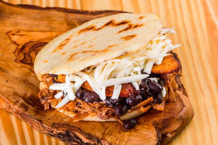 Delicious arepa stuffed with white cheese, fried plantain, roasted meat and black beans, Latin American food 版權商用圖片