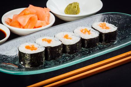 Salmon maki sushi rolls on a black background, japanese food Stok Fotoğraf