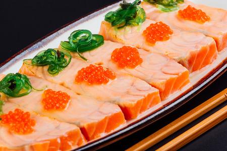 Tataki of salmon seasoned with yuzu and accompanied with salmon roe and seaweed