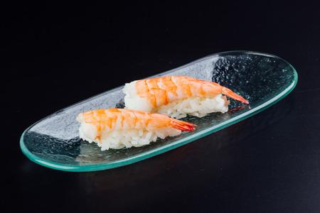 Plate with two fresh shrimp nigiris on black background