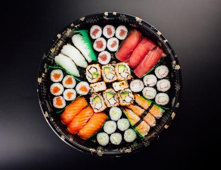Sushi Set sashimi and sushi rolls served on plastic plate and dark background 版權商用圖片 - 121475428