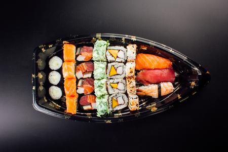 Japanese cuisine. Sushi set on a plastic ship over dark background.