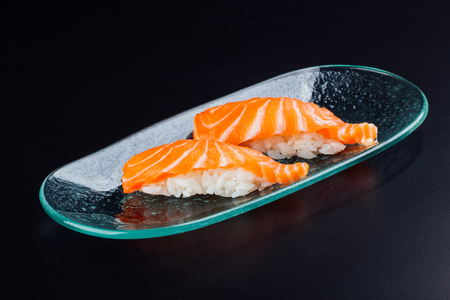 Plate with two fresh salmon nigiris on black background