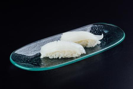 Plate with two fresh cuttlefish nigiris on black background 版權商用圖片