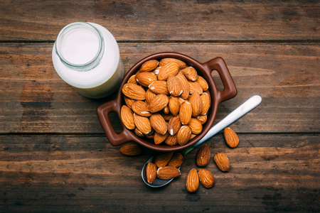 Top view of wooden table with Almond milk and several almonds in a bowl