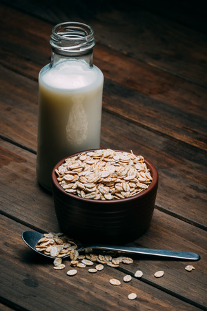 Oat milk and bowl with oat flakes on a wood background Stok Fotoğraf