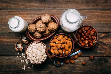 Different types of vegan milk, almond milk, oat milk, hazelnut milk and walnut milk on a wood background Stok Fotoğraf