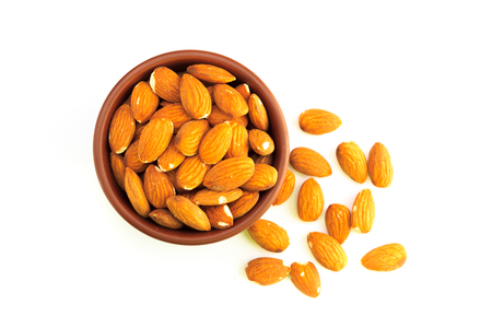 Top view of bowl full of almonds and isolated on a white background