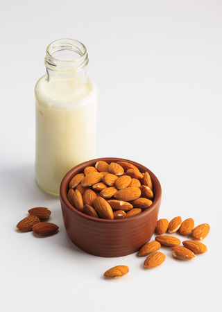 Milk and bowl of almonds isolated on a white background