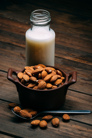 Wooden table with Almond milk and several almonds in a bowl 版權商用圖片