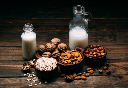 Different types of vegan milk, almond milk, oat milk, hazelnut milk and walnut milk on a wood background 版權商用圖片